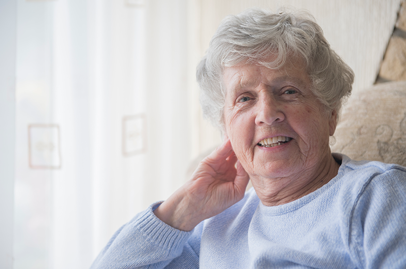 Senior Caucasian woman sitting indoors in chair smiling at camera in Sunbury Gardens