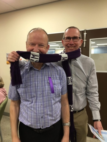 Two men wearing a football scarf.