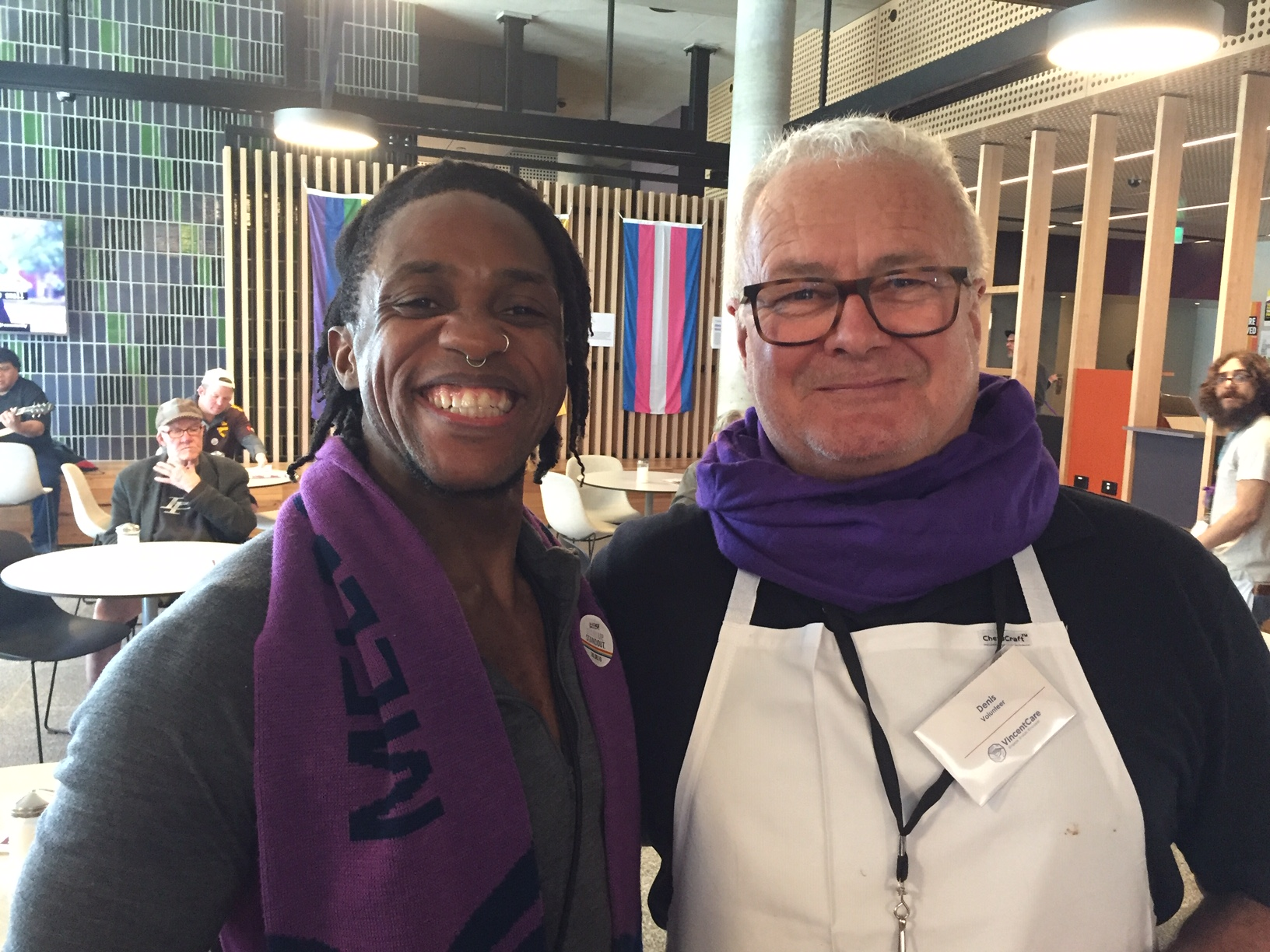 Two men wearing purple scarves