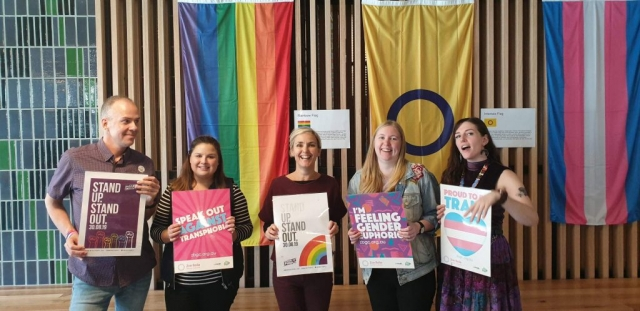 Five people standing in front of rainbow flag, intersex flag and transgender flag holding posters.