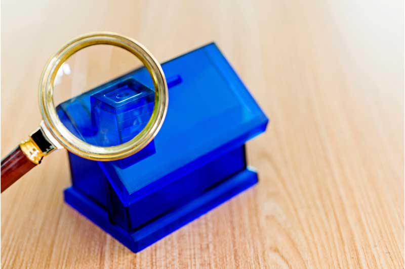 Small blue housing model with magnifying glass