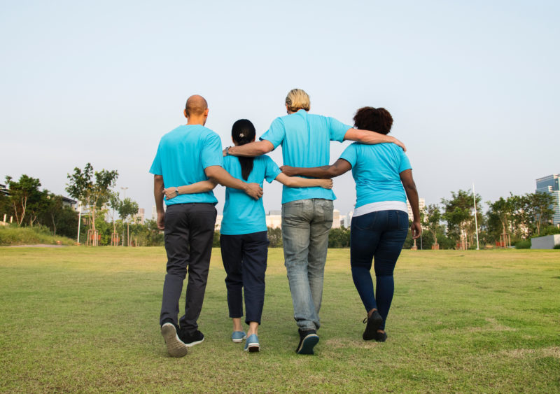 Four people wearing blue tshirts with arms around each other
