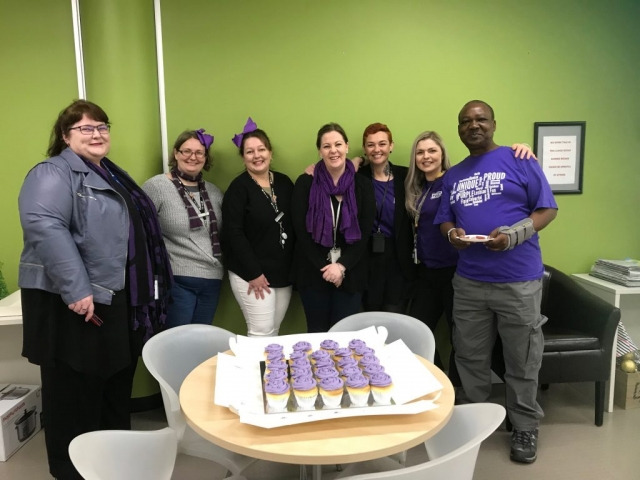 Seven people in front of purple cupcakes
