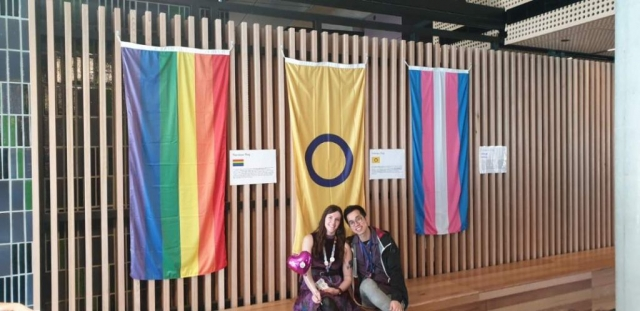 Two people sitting in front of a rainbow flag, intersex flag and transgender flag.